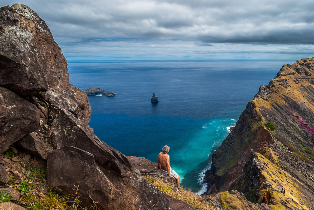Man sitting on a cliff looking out over the sea at the rim of the crater of Rano Kao Easter Island Chile