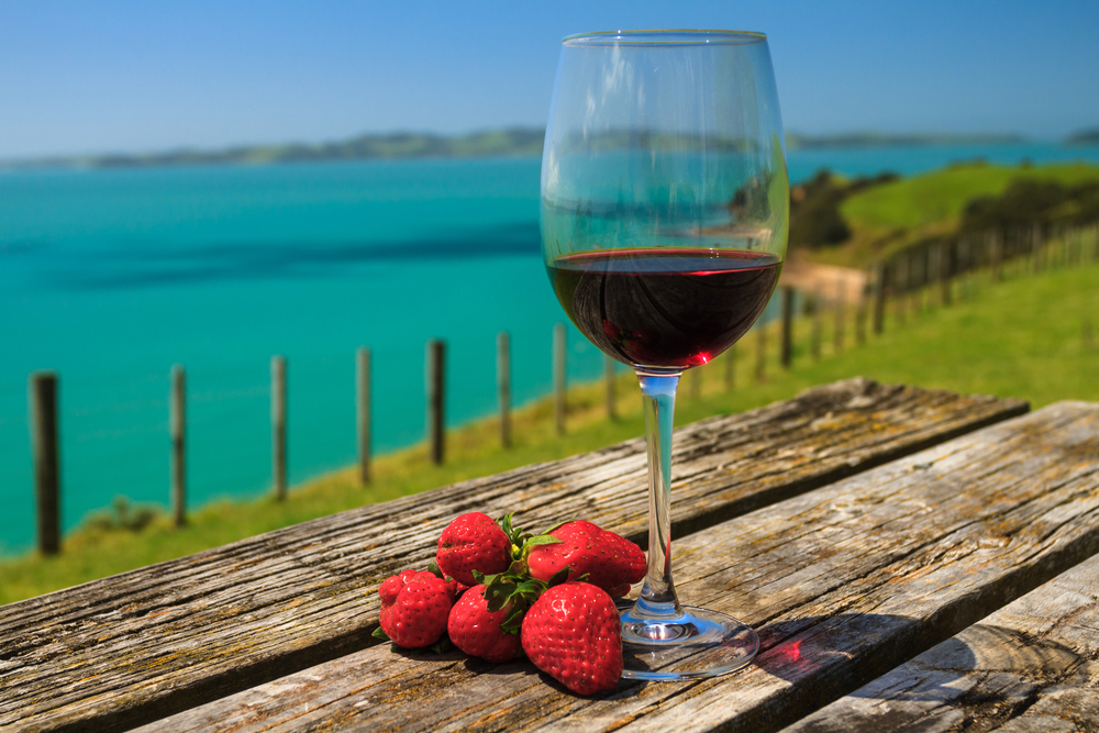 A Glass of Red Wine with Strawberry Standing on Old Table at the Beach on the Pacific Coast Auckland New Zealand