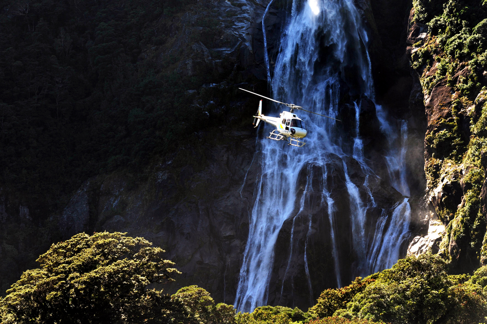 A helicopter flies over Fiordland southern New Zealand