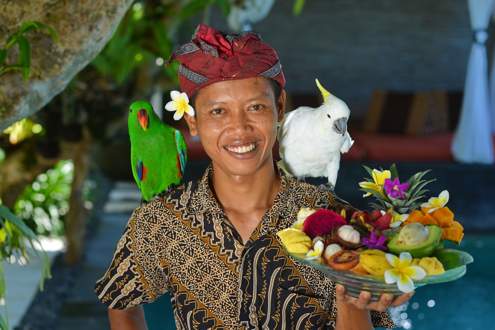 Asian waiter with a tray of tropical fruits in an exotic setting