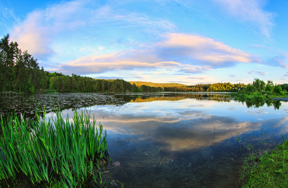 Beautiful sunset at Deweys Pond in Quechee Vermont showing the reflection of the gorgeous sunset sky in the calm waters of this pristine landmark