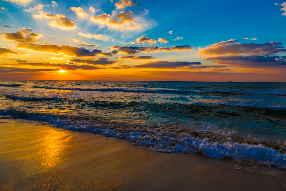 Beautiful sunset at the beach amazing colors light beam shining through the cloudscape over the arabian gulf seascape united arab emirates