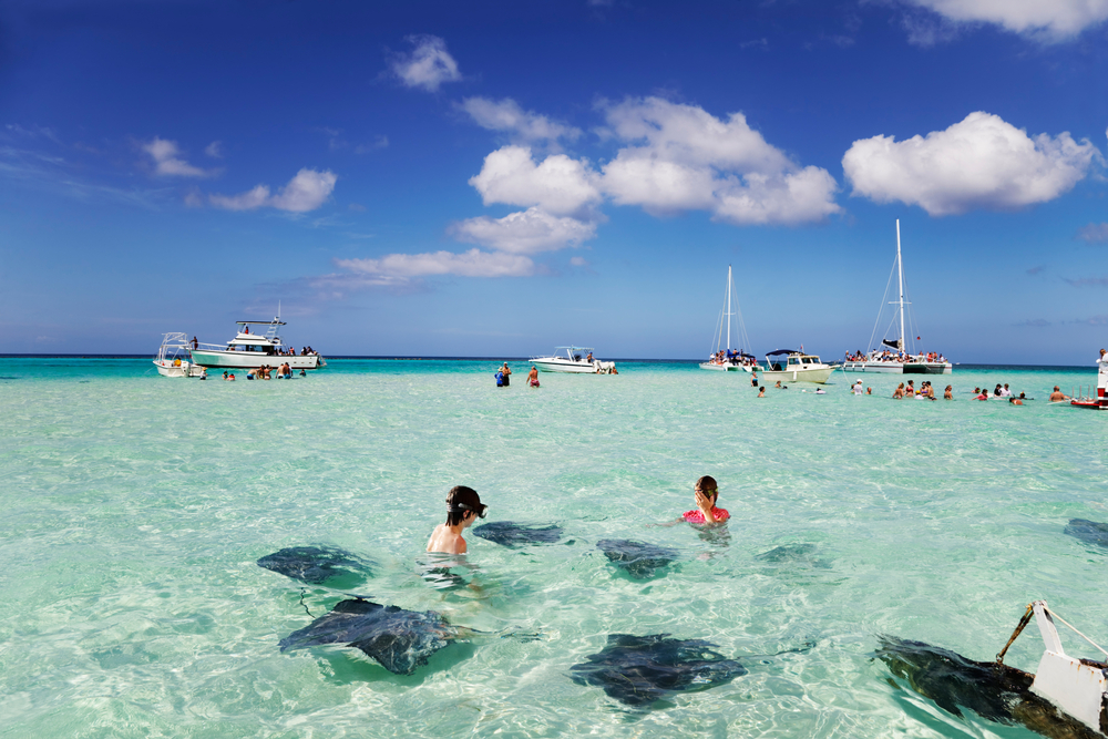 Brother sister enjoy playing with the stingrays at the sandbar off Grand Cayman