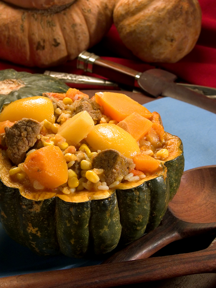 Carbonada typical food of Argentina ingredients pumpkinmaizemeat ricecarrotspeachs and potatoes serving in a pumpkin