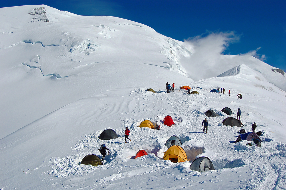 Colorful tents in high snowy mountains Refuge du Goater halfway up Mont Blanc in France