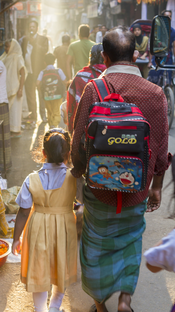 DHAKA BANGLADESH MARCH 8 2014 A man walks his daughter to school on a busy street in Old Dhaka