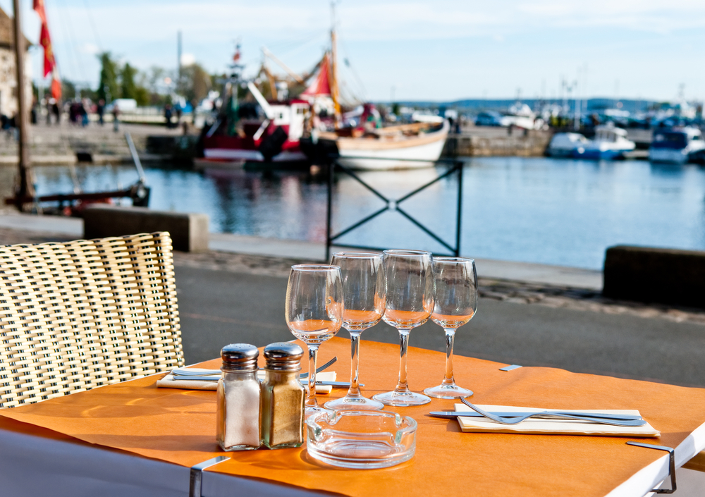 Dinner setting at harborside restaurant with sea harbor and yachts in background moody and romantic