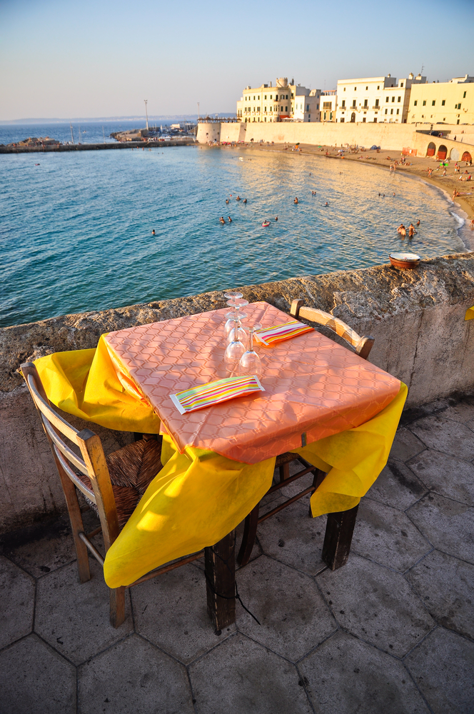 Dinner table with view on the Gallipolis beach at sunset holiday destination in Apulia Italy