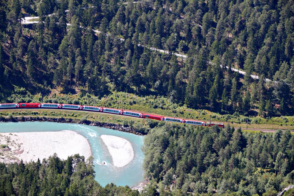 Glacier Express drives alongside river Rhine in canyon svizzera