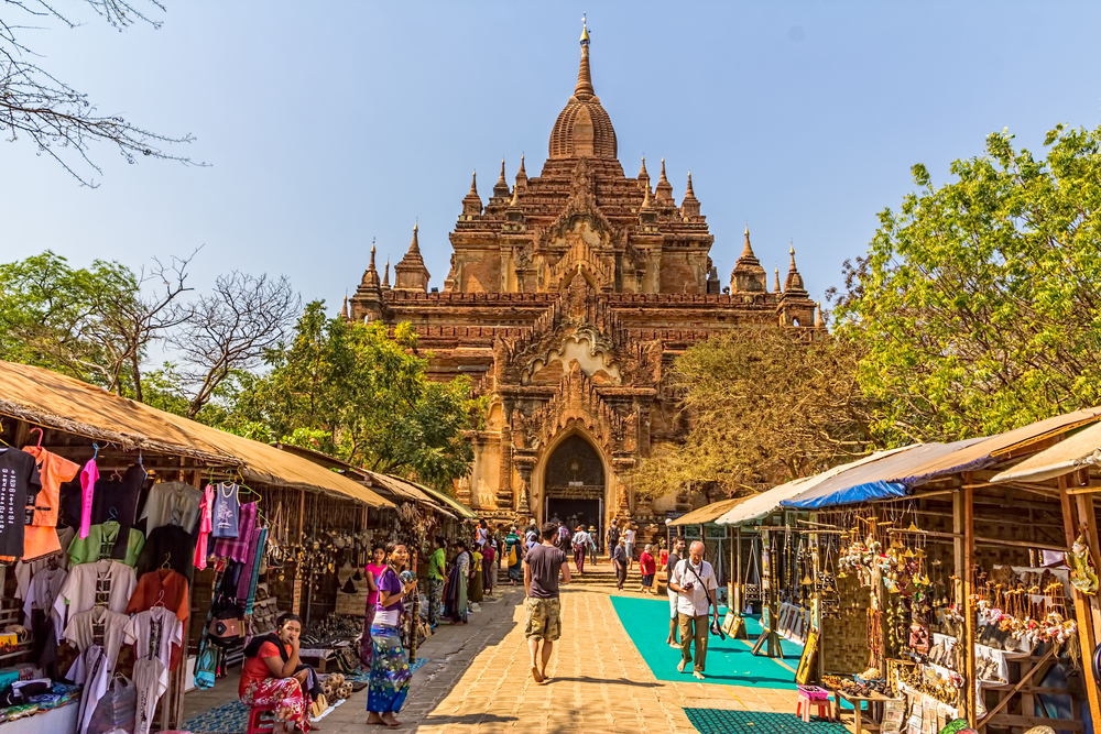 Htilominlo Temple entrance with tourist passing by street market to enter the temple on February 22 2013 in Bagan Myanmar