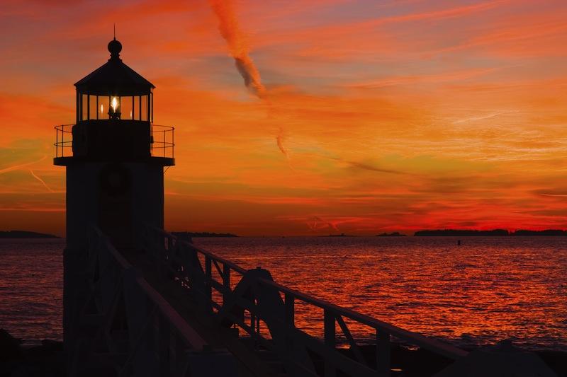 Marshall Point Lighthouse with orange sky at sunset on the coast of Maine