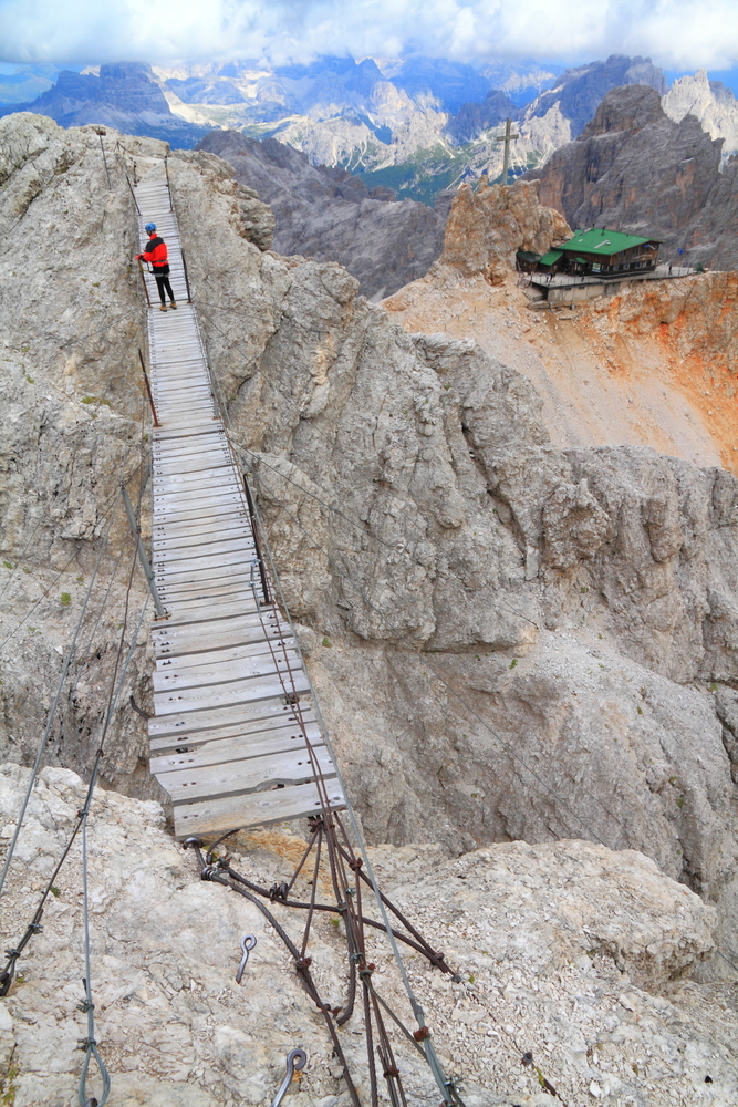 Mountaineer crossing suspension bridge to Lorenzi refuge on Monte Cristallo Dolomite Alps Italy 1