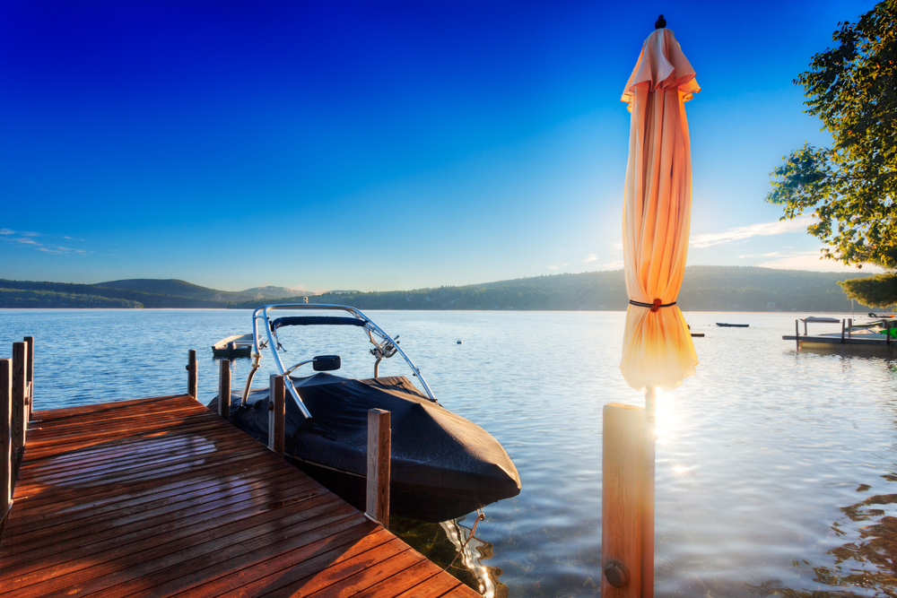 New Hampshire Lake shines behind a furled umbrella on a wood dock 10