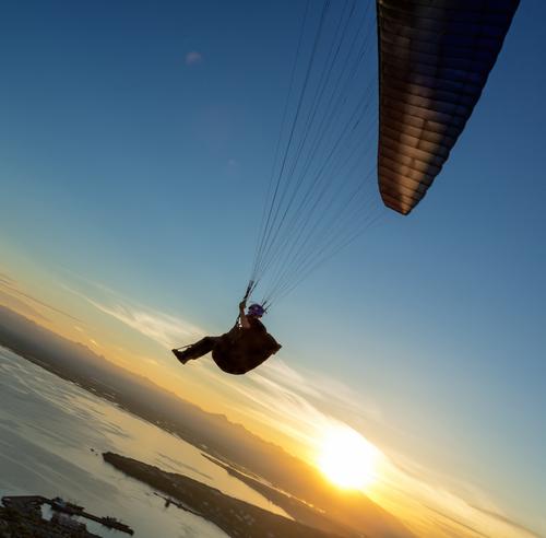 Paraglider flying over vespers Petropavlovsk Kamch atsky on the background of the Avachinsky bay at sunset Kamchatka Russia