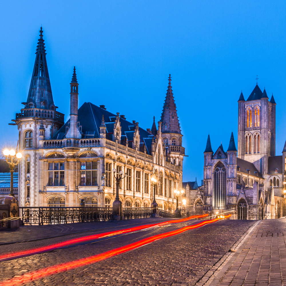 Picturesque medieval buildings around Korenmarkt square Saint Nicholas Church overlooking the bridge over Leie river in Ghent town Belgium Europe