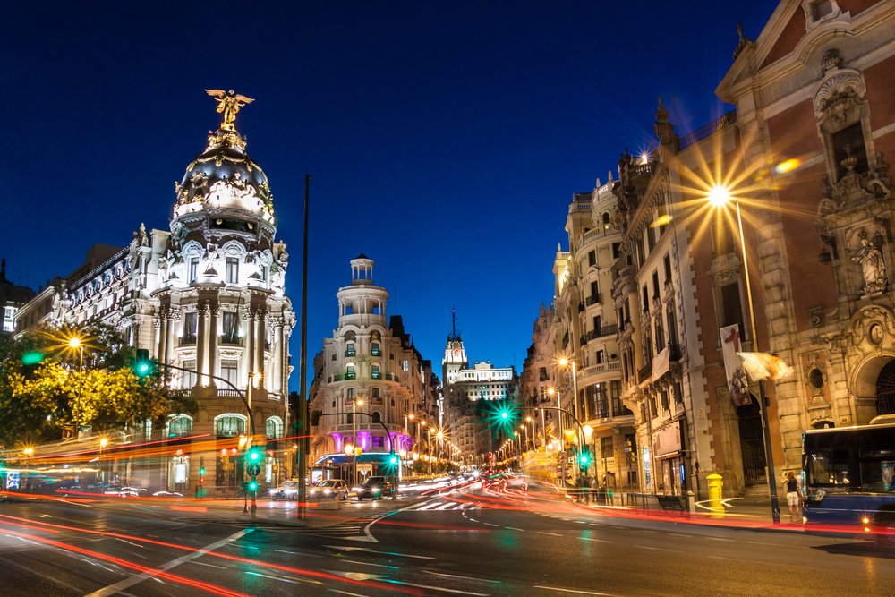 Rays of traffic lights on Gran via street main shopping street in Madrid at night