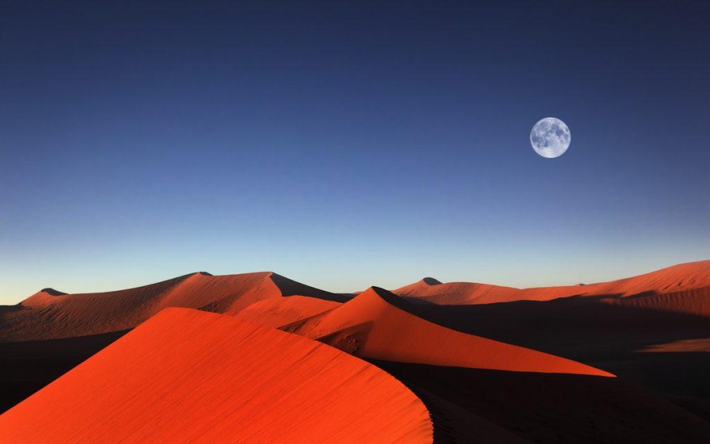 Red sand dune with full moon Sossusvlei Namibia