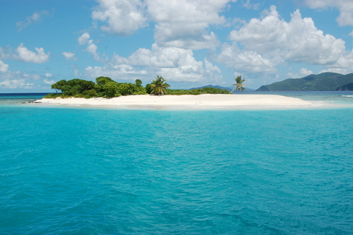 Remote island with pristine white sand surrounded by turquoise waters