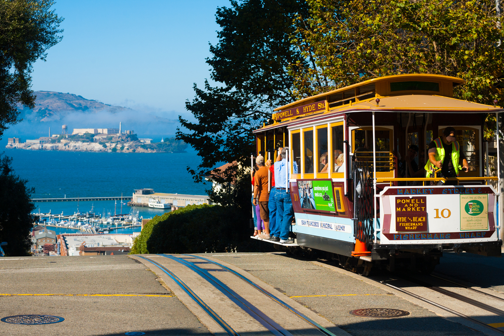 SAN FRANCISCO USA SEPTEMBER 21 Powell Hyde cable car an iconic tourist attraction descends a steep hill overlooking Alcatraz prison and SF bay on September 21 2011