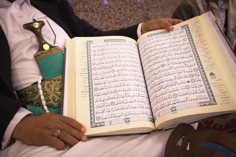 SANAA YEMEN APRIL 30 Unknown man in traditional dress holding a Koran in Sanaa Yemen on April 30 2010