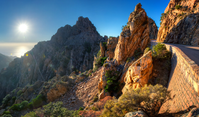 Sunset over Calanques de Piana with road through mountains in foreground Corsica France