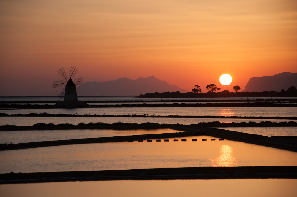 Sunset seascape view of a salt mine on the sea and a windmill in Sicily