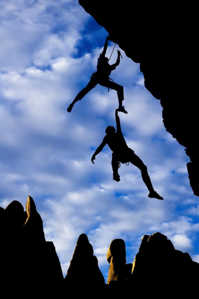 Team of climbers in trouble clinging to a cliff for dear life in The Sierra Nevada Mountains California