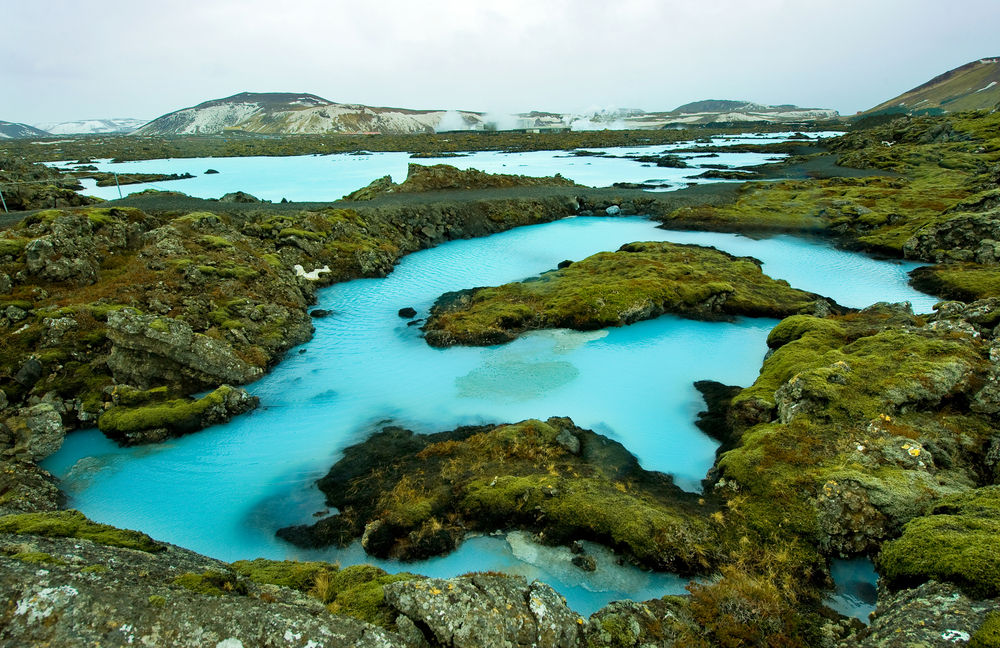 The blue water between the lava stones covered with moss just outside the Blue Lagoon resort of Iceland 9