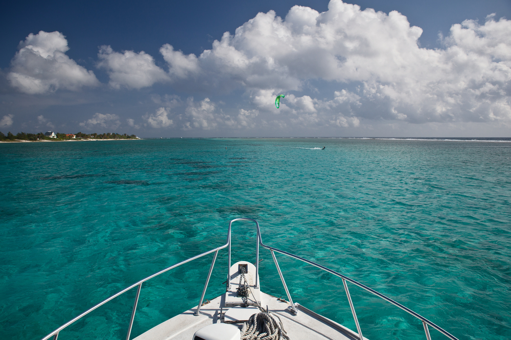 The bow of a dive boat heads out through clear shallow water towards a dive site in Grand Cayman
