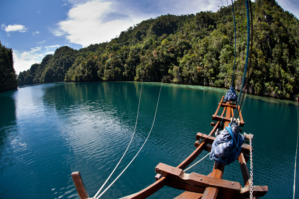 The bow of a sailing vessel is tied to limestone islands to secure it in a tight bay in Raja Ampat Indonesia