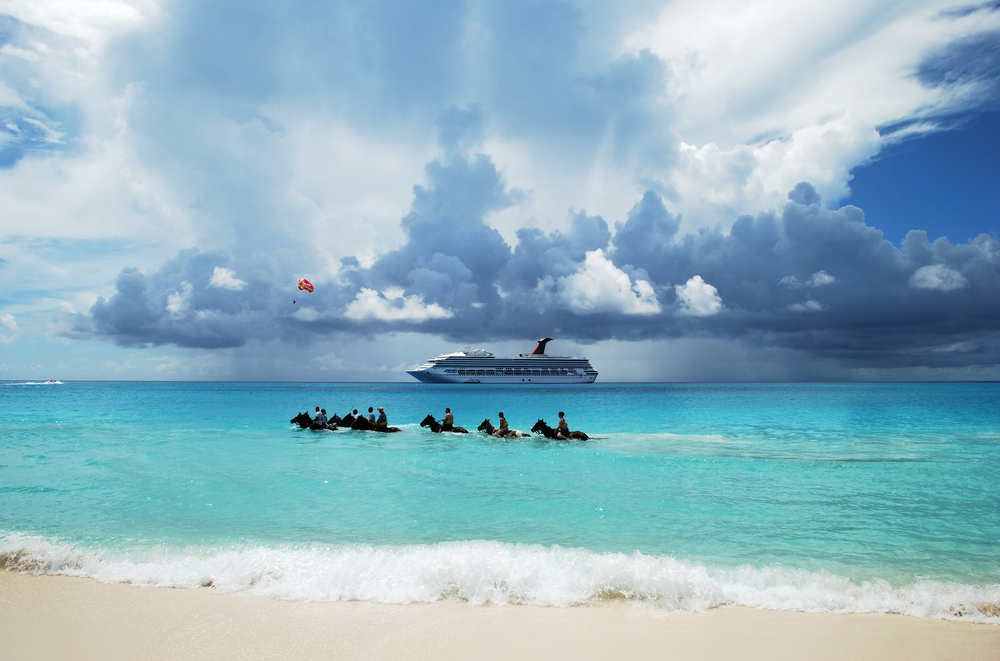 The group of tourists riding horses in Caribbean sea on Half Moon Cay The Bahamas