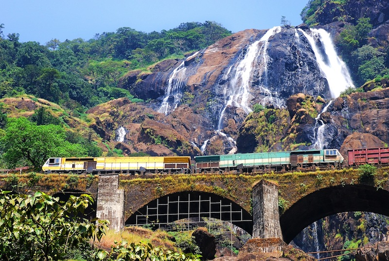 Train on the railroad bridge in the background of Dudhsagar waterfall in the state of Goa in India jpg