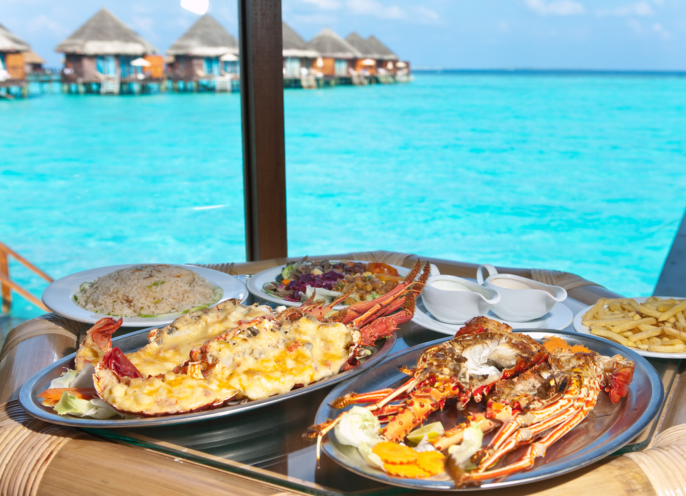 Two plates with lobster on table at window with view on ocean mldive2