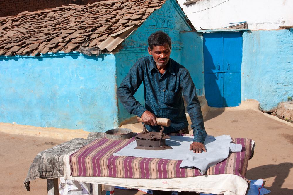 UTTAR PRADESH INDIA DEC 20 Asian man ironing clothes vintage iron on December 20 2012 in Orchha India
