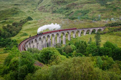 View of a steam train on a famous Glenfinnan viaduct Scotland