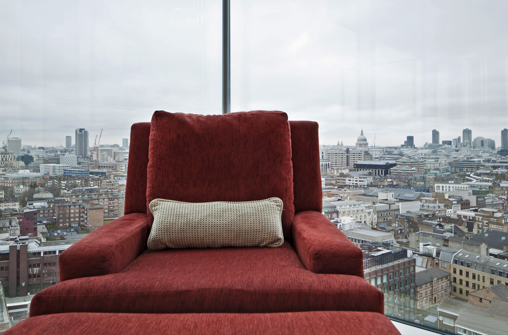 armchair in a floor to ceiling window with panoramic London views