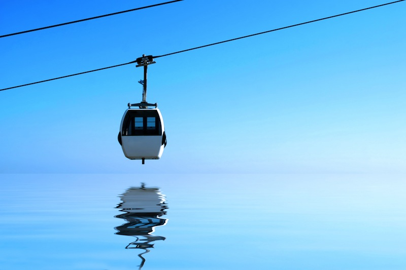 cableway in lisbon and reflection in calm and blue waters