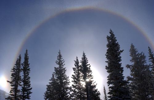 rainbow on blue sky above winter mountains