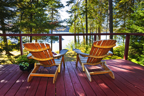 sWooden deck at forest cottage with Adirondack chairs